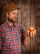 Happy farmer holding onions on rustic wood