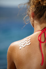 girl back with sunburn and wave of sun lotion