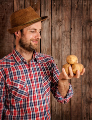 Happy farmer holding potatoes on rustic wood