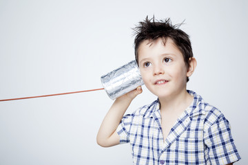 Happy child using a can as telephone against gray background