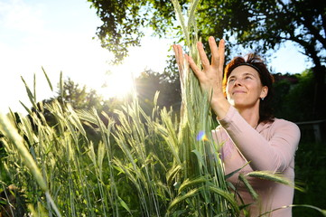 Girl tenderly embraces sheaf of wheat