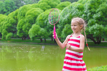 Cute little girl playing badminton on picnic
