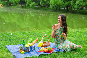 Young happy woman picnicking and relaxing outdoors