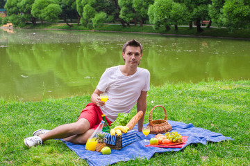 Young happy man picnicking and relaxing in the park