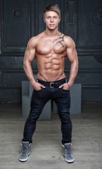 Muscular young naked sexy guy posing in jeans and shoes