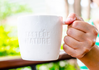"Hand holding White ceramic mug with stamp word ""Taste of nature"""