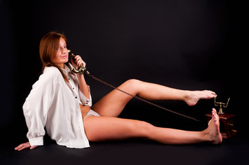 young sexy woman in white shirt with old phone