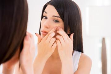 Woman examining face.