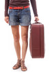 female legs in shorts and suitcase in hand