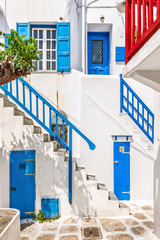 Traditional white houses with blue railing, doors and shutters i