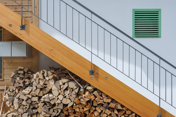 Stacked firewood, stairway and air vent of residential