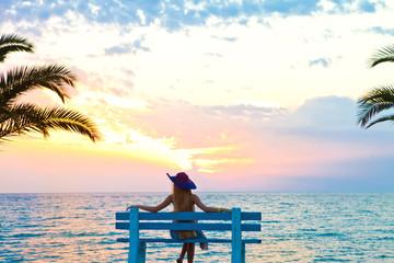 Девушка сидящая у моря на закате