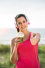 Successful female athlete drinking detox smoothie