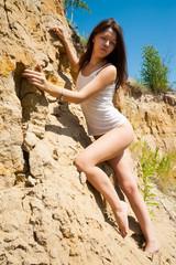 elegant nude woman climbing on sand