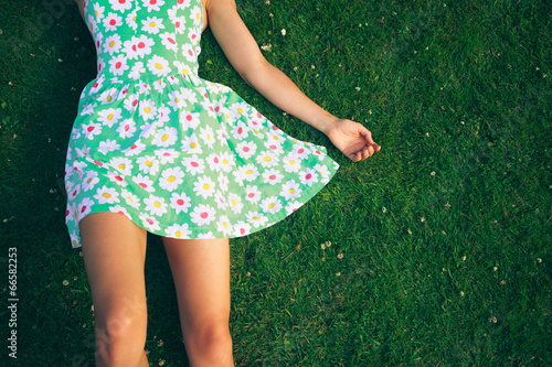 canvas print picture Young woman in dress lying on gerass