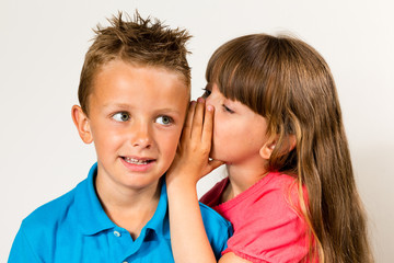Sister telling secret to brother