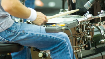 Hands drummer play music by drumsticks on the outdoor concert