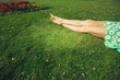 canvas print picture - The legs of a young woman lying in the grass