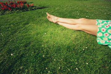 The legs of a young woman lying in the grass
