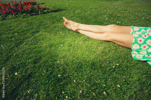 canvas print picture The legs of a young woman lying in the grass