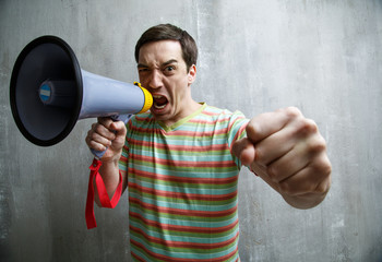 man yells into a megaphone and showing fist, against a gray text
