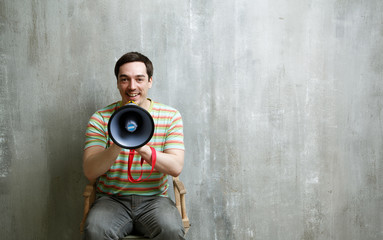 man sitting on a chair holding a megaphone and cute smiles on a