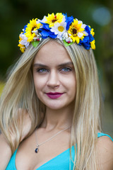 Young beautiful girl with a wreath on head of wild flowers