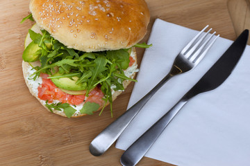Hamburger with smoked salmon, avocado and green salad