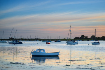 Landscape tranquil harbour at sunset with yachts in low tide