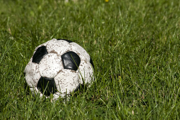 Old used grunge shabby leather soccer ball on green grass
