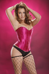 Gorgeous red-hair in sexy fishnet on magenta