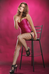 Gorgeous red-hair in sexy fishnet on a stool