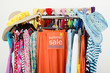 Clearance rack with colorful summer clothes and sale sign.