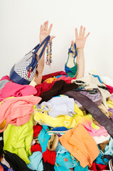 Man hands reaching out from big pile of clothes and accessories,