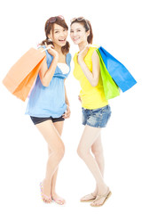 smiling young sisters standing and holding shopping bags