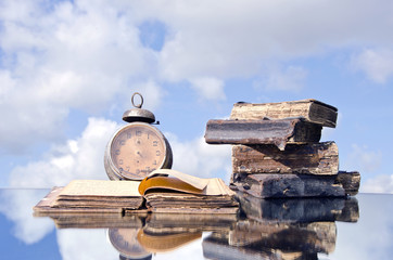 old books and vintage clock on mirror