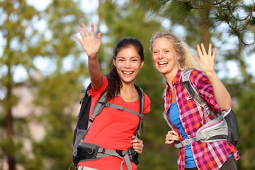Hiking women waving hello smiling at camera happy