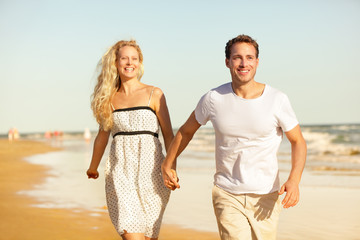 Beach couple holding hands running having fun