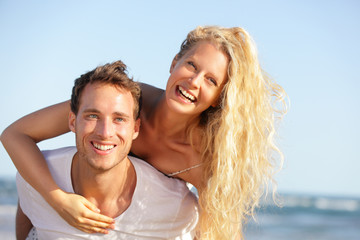 Beach couple fun - lovers on romantic travel