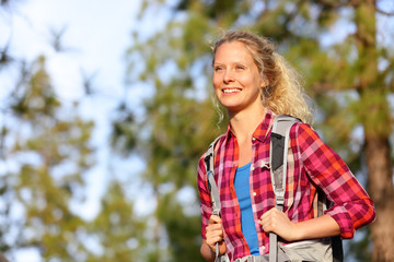 Young happy woman hiker hiking in forest