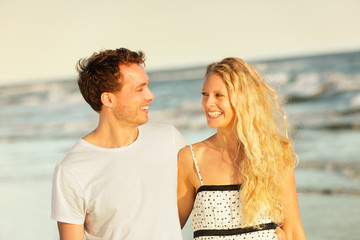 Beach couple laughing walking at romantic sunset
