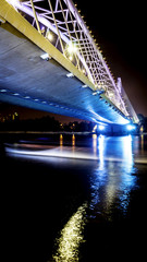 Modern bridge at night. Boat passing thru. Long exposure.
