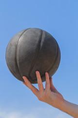 Detail of basket-ball on a daylight sky.