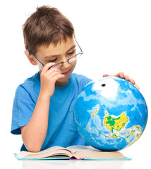 Little boy is examining globe