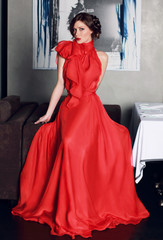 Beautiful sexy woman in red long evening dress of silk