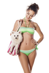 girl in a bikini carrying her little dog in a bag for the beach