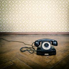 vintage old telephone, black retro phone is on the floor of used