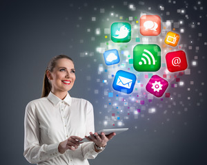Young woman with tablet and colorful media icons