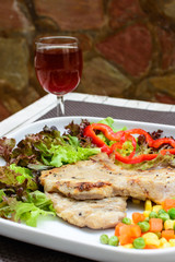 Grilled pork on white plate with glass of wine