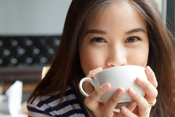Close up portrait of woman drinking coffee